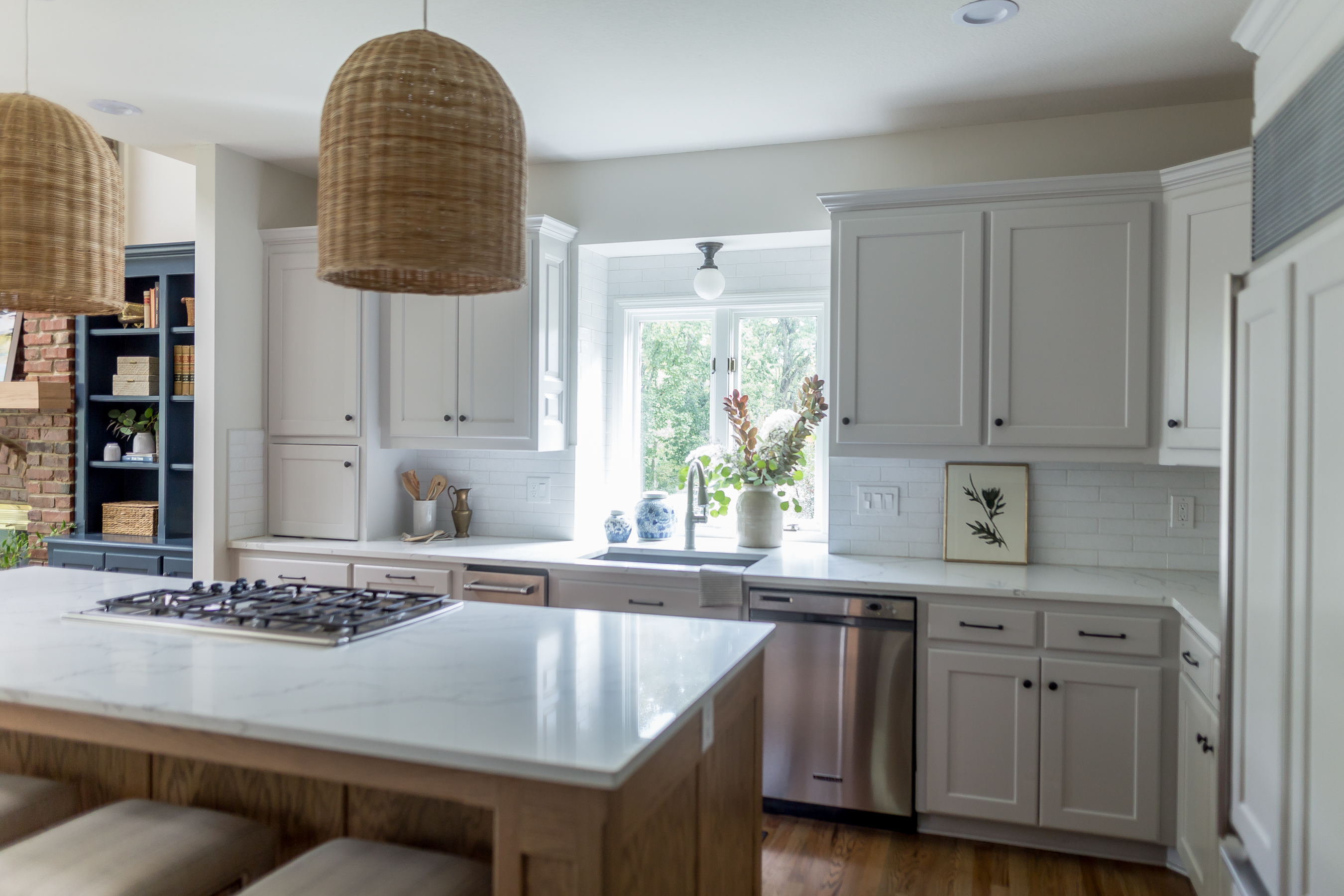 light gray cabinets with oak island, woven pendant lights, quartz countertops