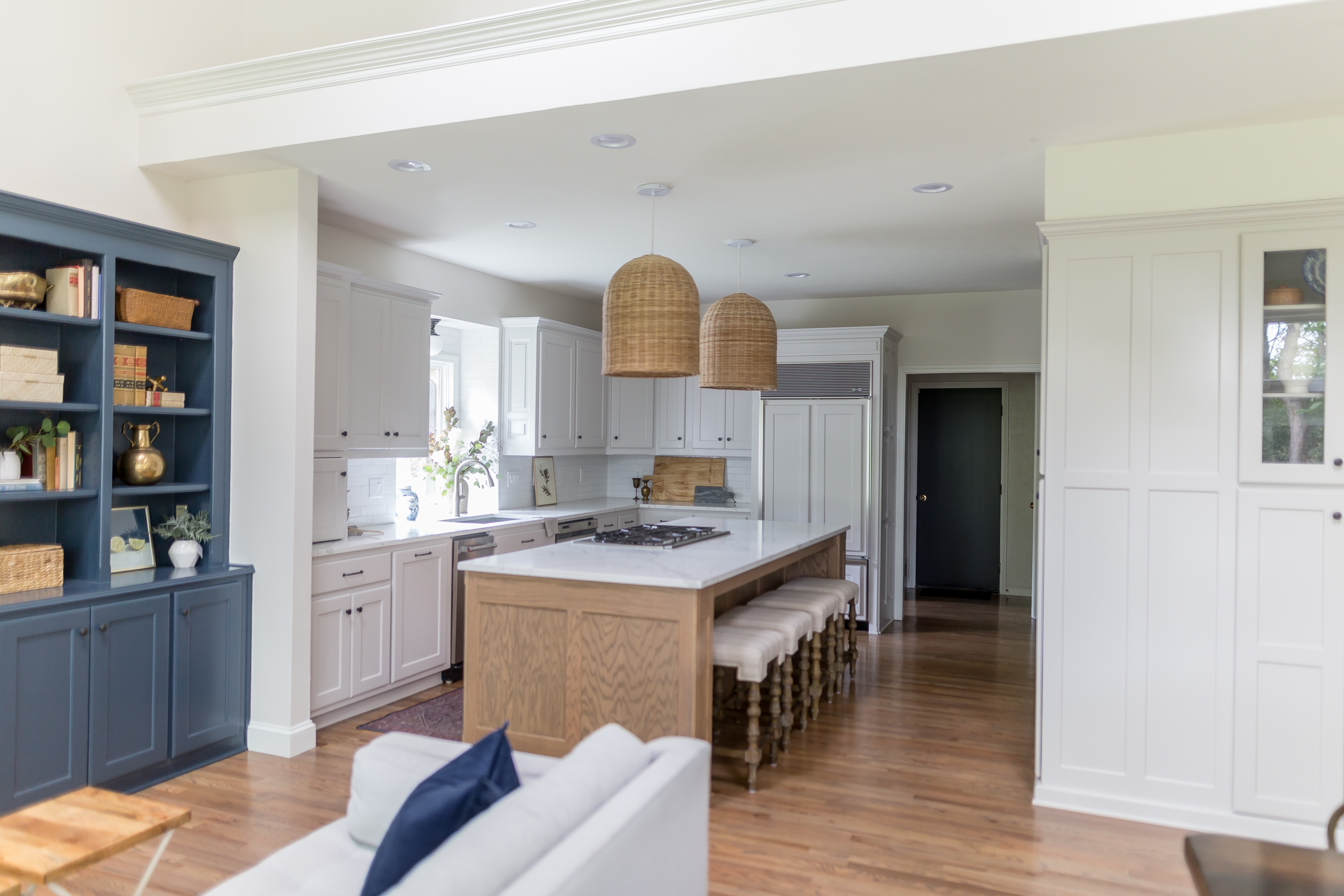 light gray cabinets with oak island, navy built ins, woven pendant lights, quartz countertops