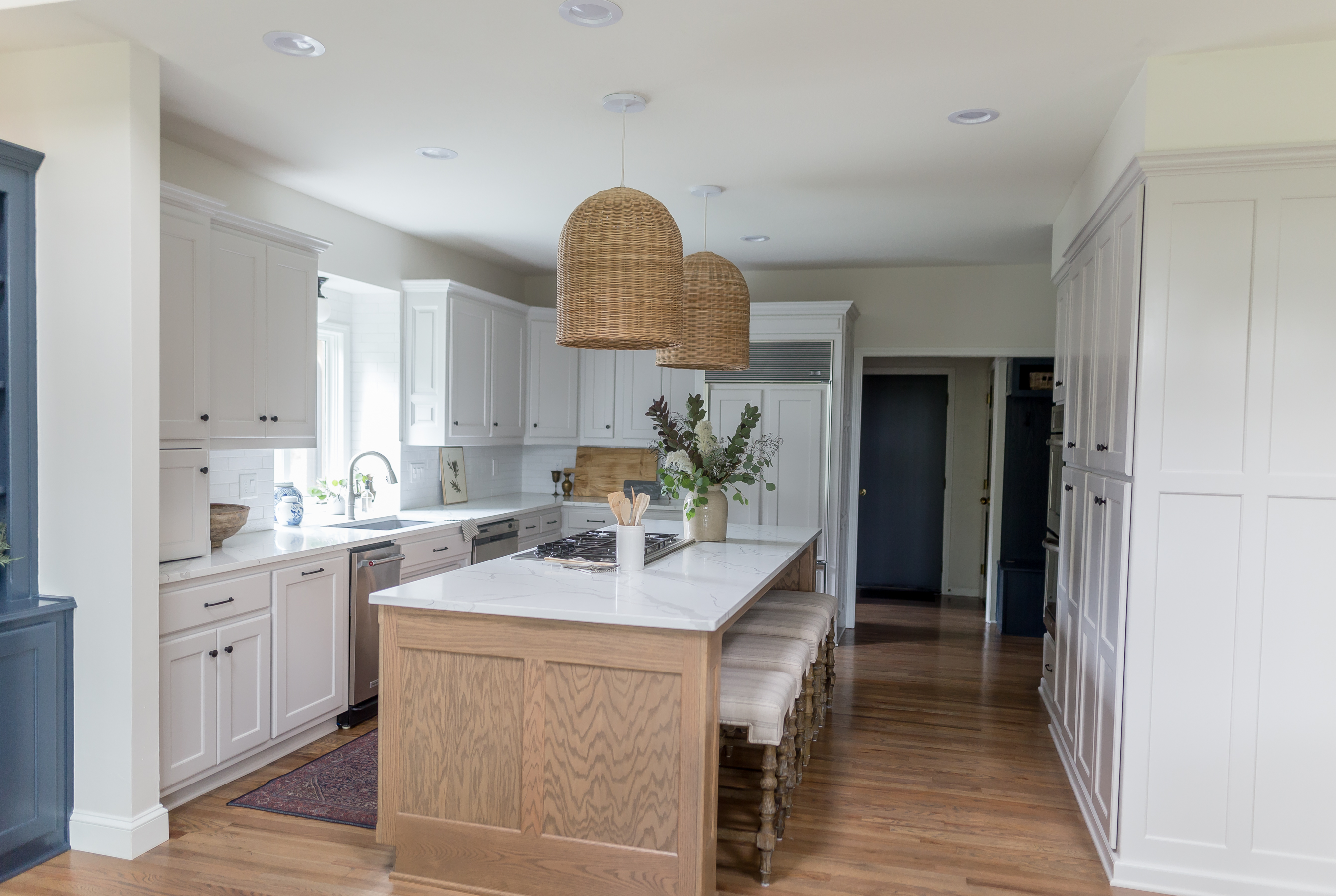 light gray cabinets with oak island, woven pendant lights, marble looking quartz countertops