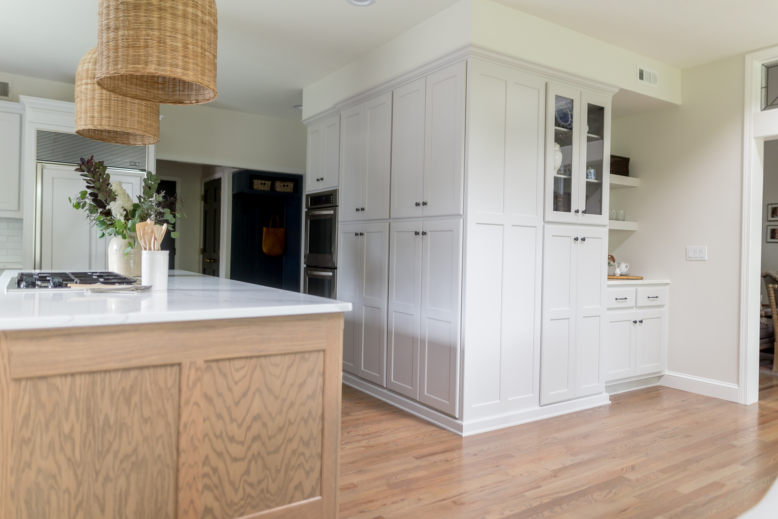 light gray cabinetry, pantry cabinets and coffee bar, woven island pendants