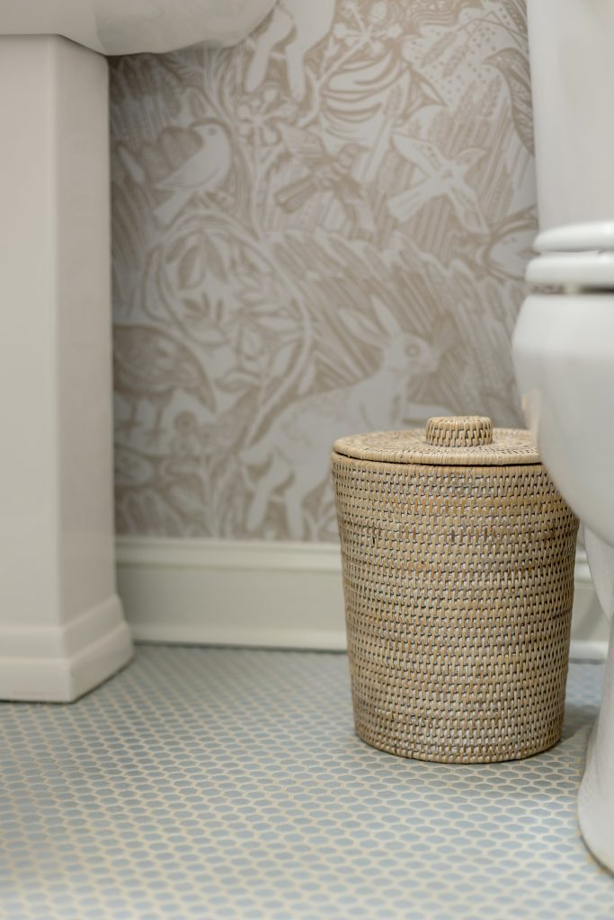 woven trash can on pale blue tile floor